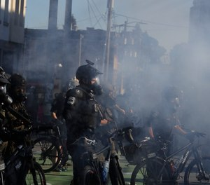Seattle police officers wear gas masks and carry weapons as smoke rises and they clash with protesters, Saturday, July 25, 2020, in Seattle.