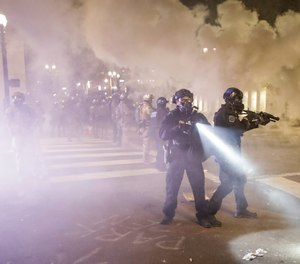 Federal officers deploy tear gas and crowd control munitions at a protest at the Mark O. Hatfield United States Courthouse Tuesday, July 28, 2020, in Portland, Ore. (AP Photo/Marcio Jose Sanchez)