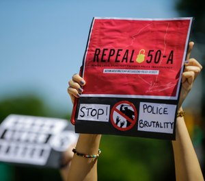 A protester holds a sign June 8, 2020 in Queens, calling for the repeal of section 50-a, a law prohibiting the public release of police officer disciplinary records. (AP Photo/Frank Franklin II, File)