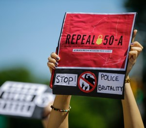 A protester holds a sign outside Queens County Criminal Court in June, calling for the repeal of section 50-a, a law prohibiting the public release of police officer and firefighter disciplinary records. State lawmakers approved the repeal earlier this year, and a judge has now rejected Buffalo fire and police unions' bids to have some records excluded from the release.