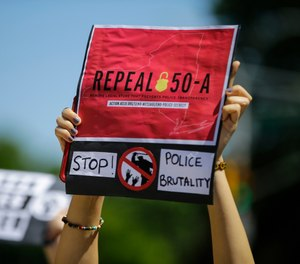 A protester holds a sign outside Queens County Criminal Court Monday, June 8, 2020, calling for the repeal of section 50-a, a law prohibiting the public release of police officer disciplinary records. (AP Photo/Frank Franklin II, File)