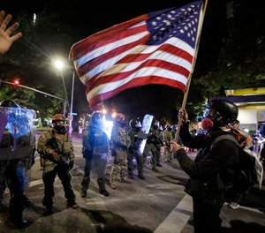 A demonstrator waves a U.S. flag in front of federal officers after tear gas is deployed during a protest at the Mark O. Hatfield United States Courthouse Thursday, July 30, 2020, in Portland, Ore. (AP Photo/Marcio Jose Sanchez)