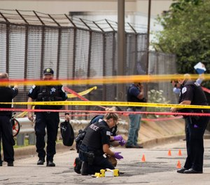 Chicago Police investigate at the 25th District station on the Northwest Side, after several officers were shot outside the station, Thursday, July 30, 2020. (Ashlee Rezin Garcia/Chicago Sun-Times via AP)