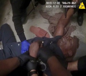 In this image made from video and released by the Forsyth County (N.C). Jail, authorities restrain John Neville in his cell as a nurse speaks with him. (Photo/Forsyth County Jail via AP)