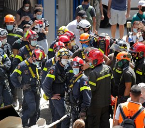 French and Lebanese firemen search in the rubble of a building after the Tuesday explosion at the seaport of Beirut, in Beirut, Lebanon, Thursday, Aug. 6, 2020. (AP Photo/Hassan Ammar)
