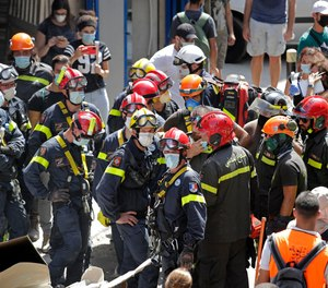 French and Lebanese firemen search in the rubble of a building after the Tuesday explosion at the seaport of Beirut, in Beirut, Lebanon, Thursday, Aug. 6, 2020.