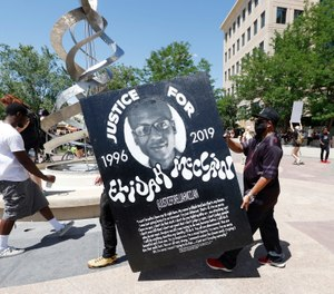 Demonstrators carry a placard during a rally and march over the death of Elijah McClain outside the police department in Aurora, Colo. The parents of McClain have filed a federal lawsuit against the officers who stopped McClain and the paramedics who administered ketamine during the stop. (AP Photo/David Zalubowski, File)