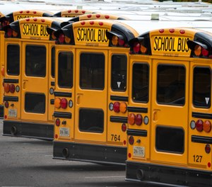 In this July 24, 2020 file photo, Fairfax County Public School buses are lined up at a maintenance facility in Lorton, Va. (AP Photo/J. Scott Applewhite)