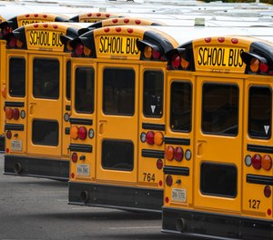 In this July 24, 2020 file photo, Fairfax County Public School buses are lined up at a maintenance facility in Lorton, Va.