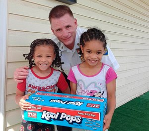 In this July 20, 2020 photo provided by Erica Dantzler, Jayden Dantzler-Clay, 5, and his sister Amiyah Dantzler-Clay, 6, hold a box of ice pops with police officer Maj. Richard Gibson at their home in Baltimore.