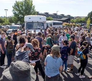 Hundreds of activists gather around two unmarked buses outside the Crane Shed Commons on Wednesday, Aug. 12, 2020, in Bend, Ore. (Ryan Brennecke/The Bulletin via AP)