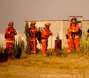 Inmate firefighters prepare to work against the River Fire in Salinas, Calif., on Monday, Aug. 17, 2020. The California Department of Corrections and Rehabilitation announced last week that eight inmate fire camps will be closing this year.