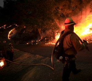 Chase Taber of CAL FIRE monitors a firing operation during the Hennessey Fire in Napa County, California. (Kent Porter/The Press Democrat via AP)