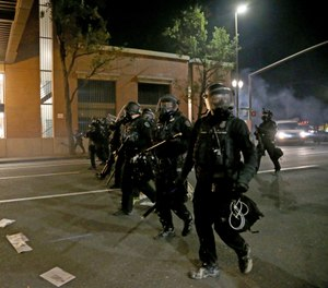 Portland police declare a riot at the Multnomah County Building, on Tuesday, Aug. 18, 2020, in Portland, Ore. (Beth Nakamura/The Oregonian via AP)