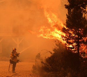 A firefighter directs water onto a tree that exploded in flames outside a house northwest of Santa Cruz, Calif. About 22,000 people in Santa Cruz and San Mateo County have self-evacuated, fleeing their homes to escape dozens of wildfires. (Photo/Shmuel Thaler, The Santa Cruz Sentinel via AP)