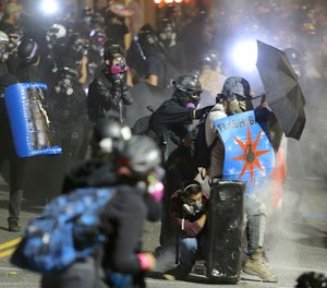 Protesters confront federal officers outside of the ICE building in Portland, Ore., Wednesday, Aug. 19, 2020. (Sean Meagher/The Oregonian via AP)