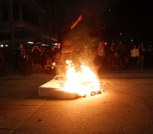 A protester jumps over a fire on his skateboard on Wednesday, Aug. 19, 2020. (Sean Meagher/The Oregonian via AP)