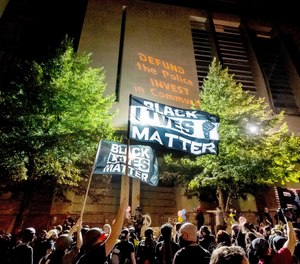 In this July 31, 2020 file photo, Black Lives Matter protesters gather at the Mark O. Hatfield United States Courthouse in Portland, Ore.