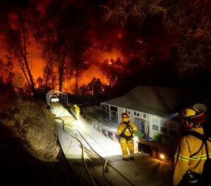 Firefighters protect a home in the Berryessa Estates neighborhood of unincorporated Napa County, Calif., as the LNU Lightning Complex fires burn on Friday, Aug. 21, 2020.