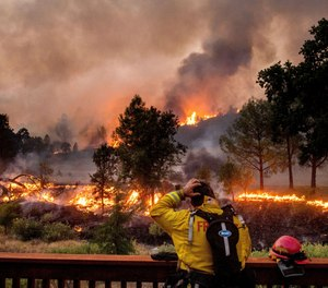 In this Aug. 21, 2020, file photo, a firefighter rubs his head while watching the LNU Lightning Complex fires spread through the Berryessa Estates neighborhood of unincorporated Napa County, Calif. Deadly wildfires in California have burned more than 4 million acres (6,250 square miles) this year — more than double the previous record for the most land burned in a single year in the state.