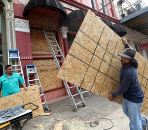 Workers set up sheets of plywood at a storefront in Galveston, Texas on Monday, Aug. 24. Hurricane Laura is expected to hit the Gulf Coast between Wednesday and Thursday and is projected to grow into a Category 3 hurricane. (Photo/Jennifer Reynolds, The Galveston County Daily News via AP)