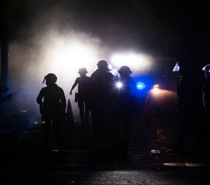A march on the Portland police union headquarters drew a rapid police response after someone set a fire next to the building Monday, Aug. 24, 2020. (Beth Nakamura/The Oregonian via AP)