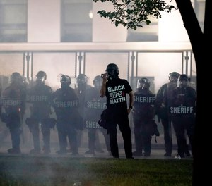 People gather Tuesday, Aug. 25, 2020 to protest in Kenosha, Wis. Anger over the Sunday shooting of Jacob Blake, a Black man, by police spilled into the streets for a third night. (AP Photo/Morry Gash)