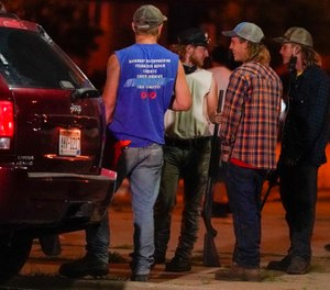 A group holds rifles as they watch protesters on the street Tuesday, Aug. 25, 2020, in Kenosha, Wis. Protests continued following the police shooting of Jacob Blake two days earlier. (AP Photo/Morry Gash)