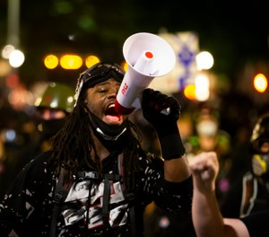 A protester uses a megaphone during a demonstration in Portland, Ore., on Tuesday, Aug. 25, 2020. (Dave Killen/The Oregonian via AP)