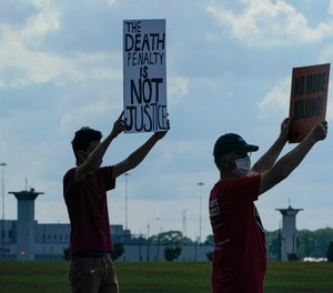 Death penalty protestors hold up signs across the street from the federal prison complex in Terre Haute, Ind. (AP Photo/Michael Conroy)