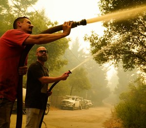 Two civilians attempt to fight the CZU Lightning Complex Fire in Bonny Doon, Calif. Some California residents have returned to evacuation zones trying to defend homes from wildfires. Fire officials warn that this could hamper official firefighting efforts. (AP Photo/Marcio Jose Sanchez)