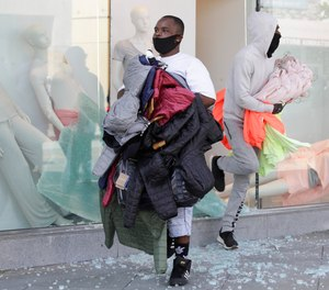 In this May 31, 2020, file photo, clothing is taken from The Gap store in Santa Monica, Calif., during unrest and protests over the death of George Floyd.