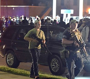Kyle Rittenhouse, left, walks along Sheridan Road in Kenosha, Wis., Tuesday, Aug. 25, 2020, with another armed civilian.