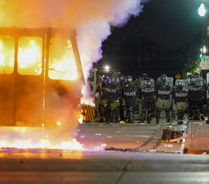 In this Aug. 24, 2020 file photo, police stand near a garbage truck ablaze during protests over the shooting of Jacob Blake in Kenosha, Wis. (AP Photo/Morry Gash, File)