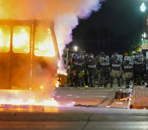 In this Aug. 24, 2020 file photo, police stand near a garbage truck ablaze during protests over the shooting of Jacob Blake in Kenosha, Wis.