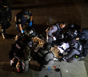 Police medics treat a man who was fatally shot during protests in Portland on Saturday. (AP Photo/Paula Bronstein)