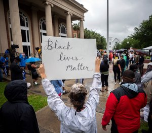 In this Thursday, June 4, 2020, file photo, a group of protesters gather outside the Glynn County Courthouse while a preliminary hearing is being held inside for Travis McMichael, Gregory McMichael and William Bryan, in Brunswick, Ga. (AP Photo/Stephen B. Morton, File)