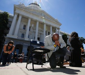In this June 9, 2020, file photo, Assemblyman Mike Gipson, D-Carson, bows his head as he and other members of the California Legislature kneel for George Floyd at the Capitol in Sacramento, Calif. (AP Photo/Rich Pedroncelli, File)