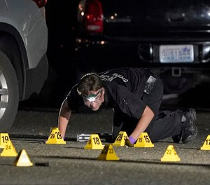 A Washington State Patrol Crime Lab worker looks at evidence markers in the early morning hours of Friday, Sept. 4, 2020, in Lacey, Wash. (AP Photo/Ted S. Warren)