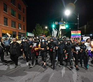 Demonstrators march along a street in Rochester, N.Y., Friday, Sept. 4, 2020, during a protest over the death of Daniel Prude. (AP Photo/Adrian Kraus)