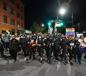 Demonstrators march along a street in Rochester, N.Y., Friday, Sept. 4, 2020, during a protest over the death of Daniel Prude.