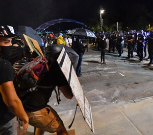 Demonstrators clash with police officers a block from the Public Safety Building in Rochester, N.Y., Friday, Sept. 4, 2020, after a rally and march protesting the death of Daniel Prude. (AP Photo/Adrian Kraus)
