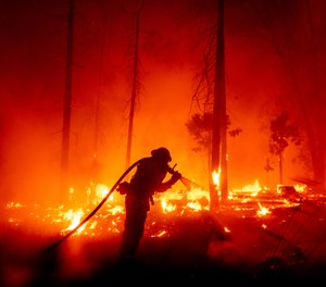 A firefighter battles the Creek Fire as it threatens homes in Madera County, Calif. Wildfires in California this year have set a new record, burning more than 2 million acres across the state. (AP Photo/Noah Berger)