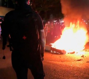 In this image taken from video a mattress burns in the street near the Portland Police Bureau's North Precinct Sunday night, Sept. 6, 2020, in Portland, Ore.