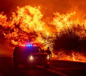 Flames lick above vehicles on Highway 162 as the Bear Fire burns in Oroville, Calif., on Wednesday, Sept. 9, 2020. The Bear Fire has exploded in size, killing three and threatening the community of Paradise, which was devastated by the 2018 Camp Fire.