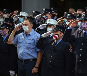 Firefighters salute in front of FDNY Ladder 10 Engine 10 near the 9/11 Memorial on Friday, Sept. 11, 2020, in New York. The federal government has agreed to pay back $3.3 million it took from the FDNY's 9/11 health program over the last four years.