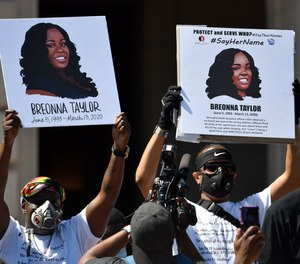 Signs are held up showing Breonna Taylor during a rally in her honor on the steps of the Kentucky State Capitol in Frankfort, Ky., Thursday, June 25, 2020. A Kentucky EMT who treated one of the officers involved in Taylor's fatal shooting has been placed on leave after posting about the case on Facebook.