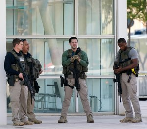 Federal law enforcement personnel stand outside the Sandra Day O'Connor Federal Courthouse Tuesday, Sept. 15, 2020, in Phoenix. (AP Photo/Ross D. Franklin)