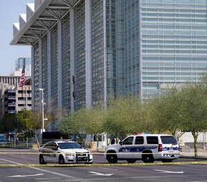 Police cars close off a street outside the Sandra Day O'Connor U.S. Courthouse in Phoenix, on Tuesday, Sept. 15, 2020.  (AP Photo/Ross D. Franklin)