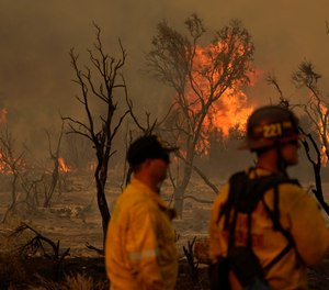 Members of the San Bernardino County Fire Department keep an eye on a flareup from the Bobcat Fire on Saturday, Sept. 19, 2020, in Valyermo, Calif. The Bobcat Fire doubled in size over the last week, becoming one of Los Angeles County's largest-ever wildfires. (AP Photo/Marcio Jose Sanchez)
